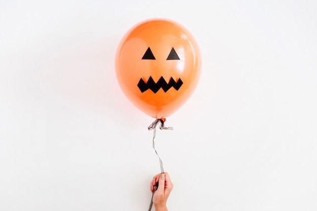Halloween minimal concept. one orange balloon with scary face in girl's hand on white