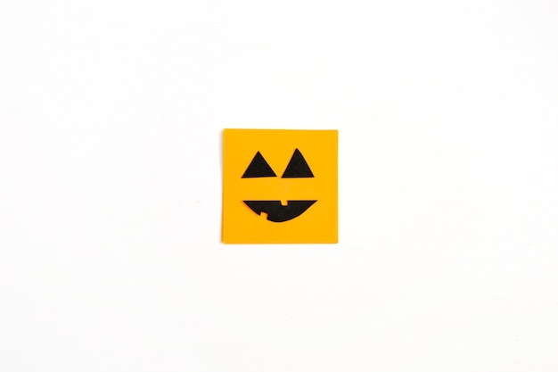 Halloween minimal concept. orange paper with funny face on white