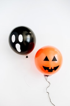 Halloween minimal concept. two balloons with funny smiling and scary faces on white