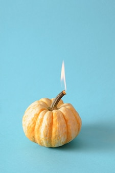 燃えるカボチャとハロウィーンの最小限のコンセプト。創造的な秋の休日の青い背景