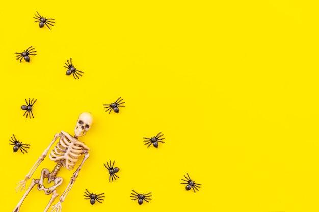 할로윈 최소한의 장식, 많은 검은 거미와 해골이 노란색 배경에 격리된 구성. 할로윈 축하 트릭 또는 치료 개념. 평평한 평면도 복사 공간.