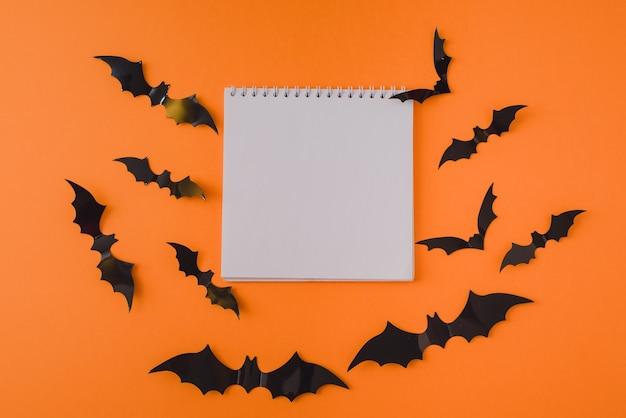 オレンジ色の背景に黒いコウモリとハロウィーンのモックアップ。おめでとうや招待状のバナー。コピースペースのあるフラットな上面図。空白のメモ帳。スペースをコピーします。