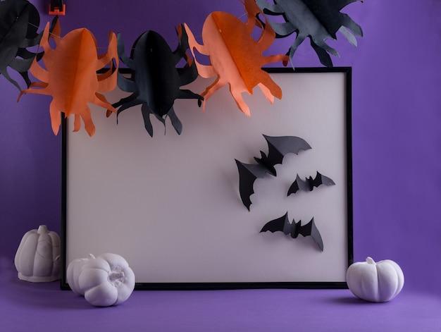 Макет хэллоуина с рамкой, черными бумажными летучими мышами и белыми декоративными тыквами на цветном фиолетовом фоне.