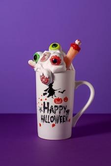 紫色の背景に背の高いマグカップでハロウィンモンスターを振る。目、指、脳、頭蓋骨のキャンディが入ったホイップクリーム。不気味な飲み物。