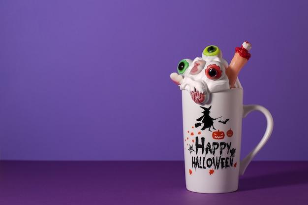 ハロウィンモンスターは、コピースペースと紫色の背景に背の高いマグカップで振る。目、指、脳、頭蓋骨のキャンディが入ったホイップクリーム。不気味な飲み物。