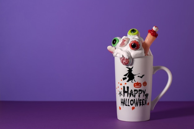 Halloween monster shake in tall mug on purple background with copy space. whipped cream with eyes, finger, brain and skull candy. creepy drink.