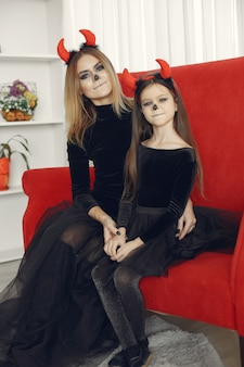 ハロウィン。ハロウィーンの衣装の母と娘。自宅で家族。