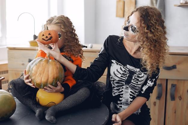 Хэллоуин. мать и дочь в костюме хэллоуина в мексиканском стиле. семья дома с тыквами.