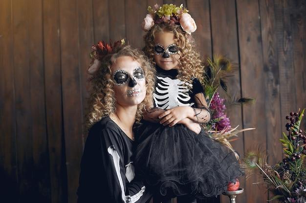 Хэллоуин. мать и дочь в костюме хэллоуина в мексиканском стиле. семья дома.