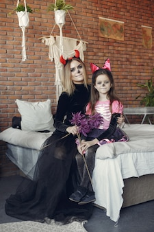 Halloween. mother and daughter in halloween costume. family at home.