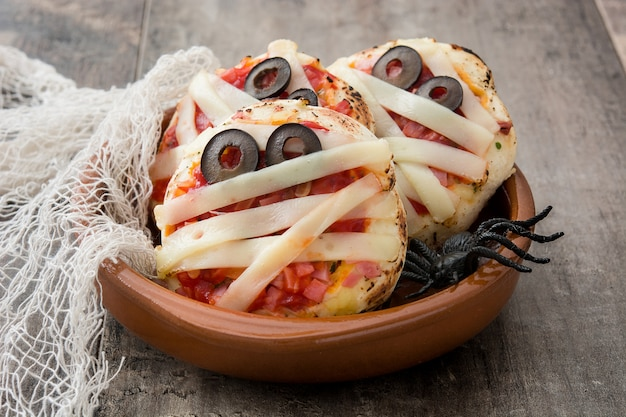 Мини-пицца мумии хэллоуина на деревянном столе