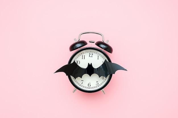 ハロウィーンの夜のコンセプト。ピンクの背景に黒の目覚まし時計とフェイスクロックのバット。クリエイティブフラットレイ