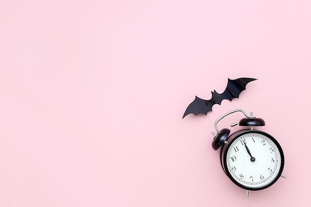 ハロウィーンの夜のコンセプト。ピンクの背景に黒の目覚まし時計とフライングバット。クリエイティブフラットレイ、トップビュー