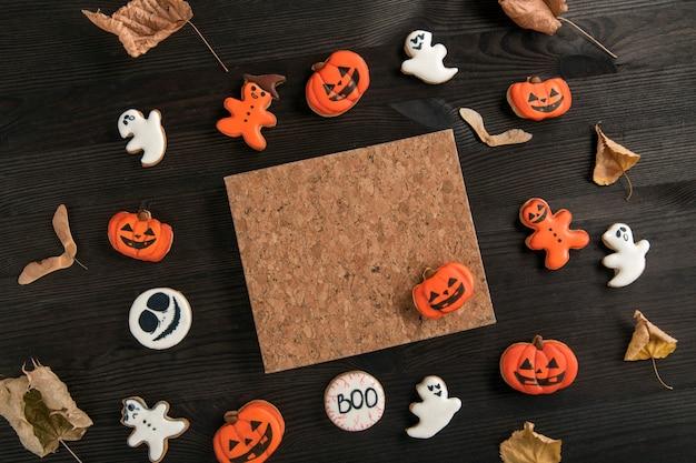 ハロウィーンのオレンジと白のジンジャーブレッドクッキーは、暗い木製のテーブルの上にあります。自家製クッキーとハロウィーンのコンセプト。コピースペース
