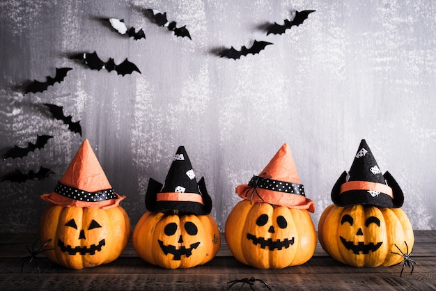 Halloween, orange ghost pumpkins with witch hat on gray wooden board