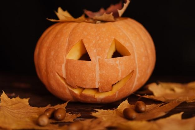 Halloween orange pumpkin with maple leaves and acorns