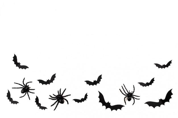 ハロウィーンのペーパーアート。白地に黒い紙コウモリとクモを飛んでいます。
