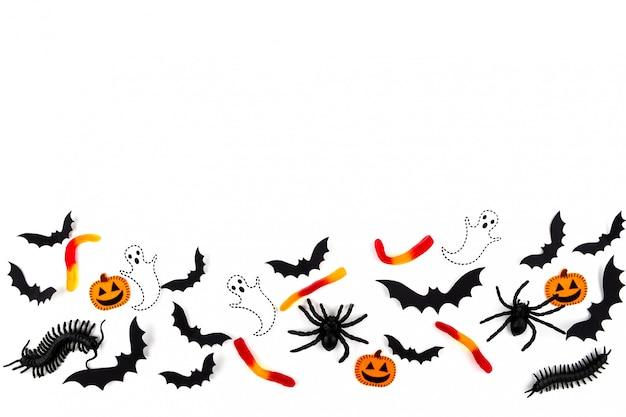 ハロウィーンのペーパーアート。黒い紙コウモリ、カブトムシ、クモ、キャンディー、カボチャ、白の幽霊を飛んでいます。