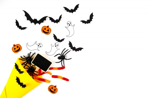 Halloween paper art. flying black paper bats, beetles and spiders, candys, pumpkins and ghosts on white.