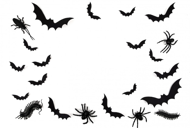 Halloween paper art. flying black paper bats, beetles and spiders on white.