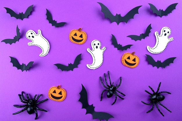 Искусство бумаги хэллоуина. летучие мыши из черной бумаги, тыквы и привидения на фиолетовом.