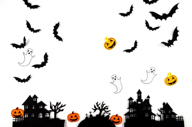 ハロウィーンのペーパーアート。白地に黒い紙コウモリ、カボチャ、幽霊を飛んでいます。