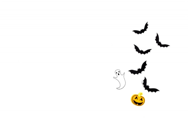 Halloween paper art. flying black paper bats, pumpkins and ghosts on white.