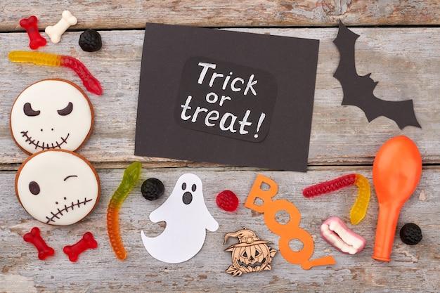 ハロウィーンの紙の装飾とキャンディークッキーと紙dでハロウィーンの休日の背景を扱います...