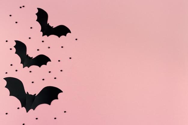 ハロウィーンペーパーデコレーションコピースペースとパステルピンクの背景に黒コウモリ。フラット横たわっていた。上面図。