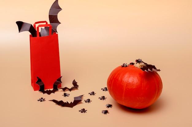 ハロウィーンパーティーのコンセプト。ベージュの背景に、コウモリ、ハエ、カボチャが入った赤いパッケージ。コピースペースのクローズアップ付き。