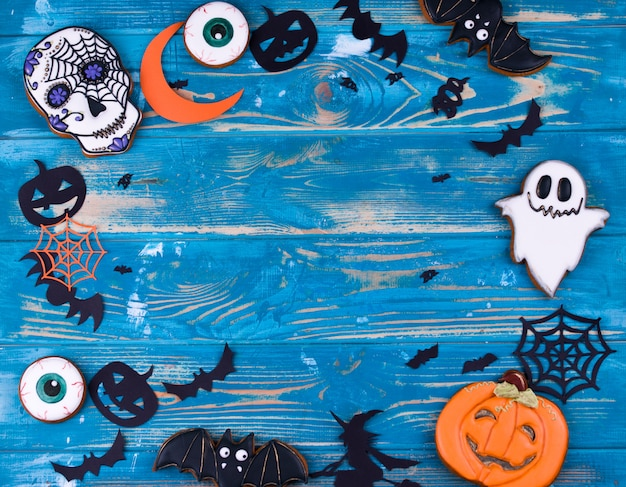 Halloween party content. halloween gingerbread cookies on the blue wood background.