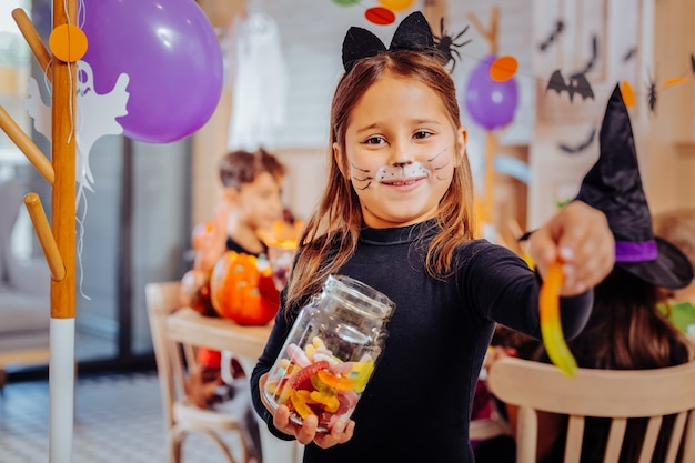 Halloween party. dark-eyed beautiful cute girl wearing cat suit eating gummy worm while attending halloween party
