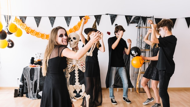 Halloween party in decorated room with balloons and skeleton