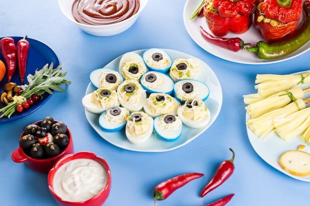 Еда вечеринки в честь хэллоуина на синем столе