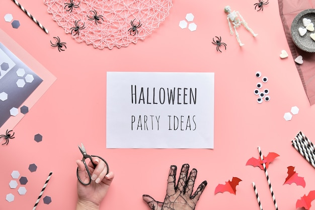 Halloween party ideas text on white page held in hand. flat lay with scissors and decorations on pink paper
