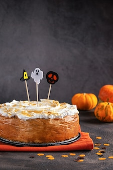 Halloween party pumpkin cheesecake with marshmallow meringue topping decorated with topper