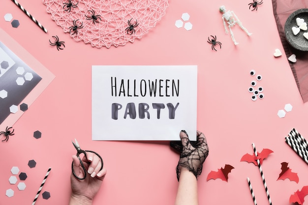 Halloween party text on white page held in hand. flat lay with black and white decorations, hand hold page with text