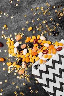 할로윈 파티 트릭 오브 트릿 캔디는 어두운 나무 배경에 있는 파티 호의 가방에서 흘러내리는 사탕을 가지고 있습니다.