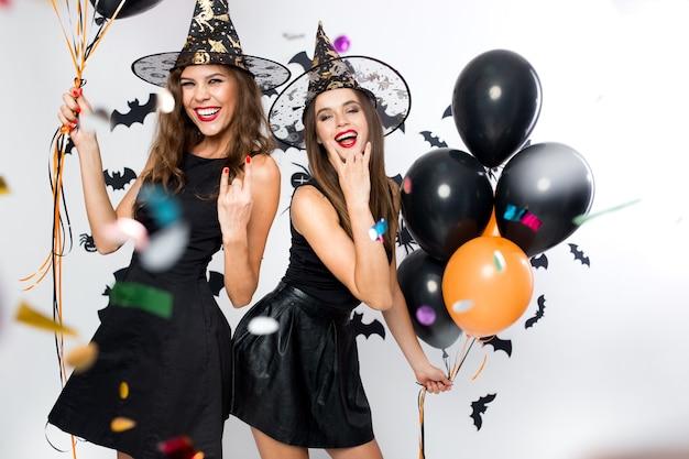 할로윈 파티. 검은 드레스와 마녀 모자를 쓴 두 명의 멋진 소녀가 풍선과 색종이 조각으로 즐거운 시간을 보냅니다. .