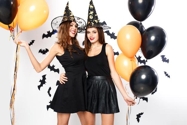 할로윈 파티. 검은 드레스와 마녀 모자를 쓴 두 명의 멋진 여성이 박쥐가 있는 벽 배경에 검은색과 주황색 풍선을 들고 있습니다. .