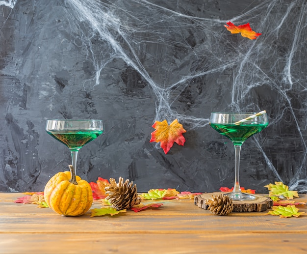 Halloween party with green cocktails and  little pumpkin, side view with copyspace