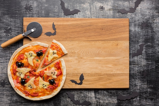 Halloween pizza slices on wooden board