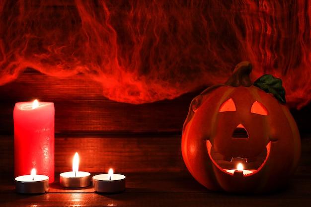 Открытка на хэллоуин с копией пространства jackolatern и свечами на фоне паутины