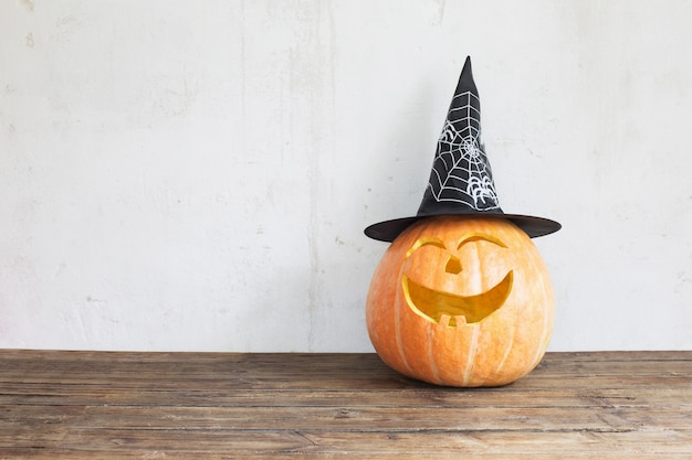 Halloween pumpkin in black hat on wooden table