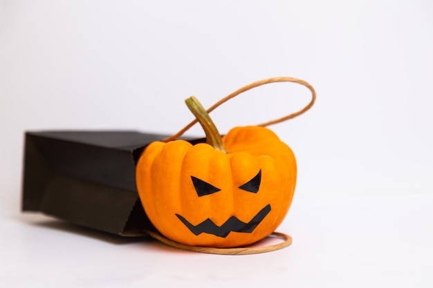 Halloween pumpkin and black paper bag isolated