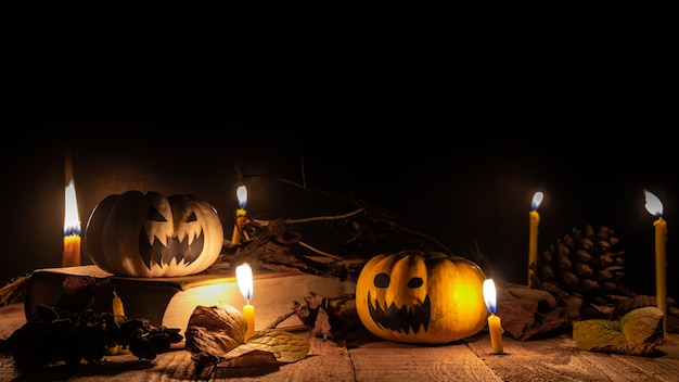 Halloween pumpkin on books with around burning candle. halloween concept.