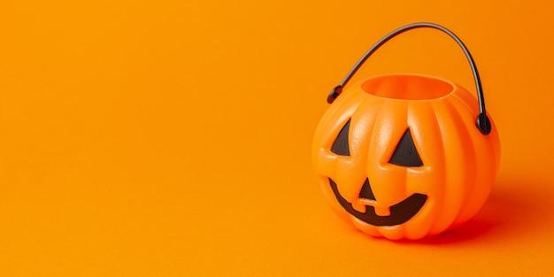 Halloween. pumpkin candy basket on an orange background.