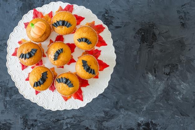 Halloween pumpkin cupcakes served on black , , top view, flat lay, copyspace