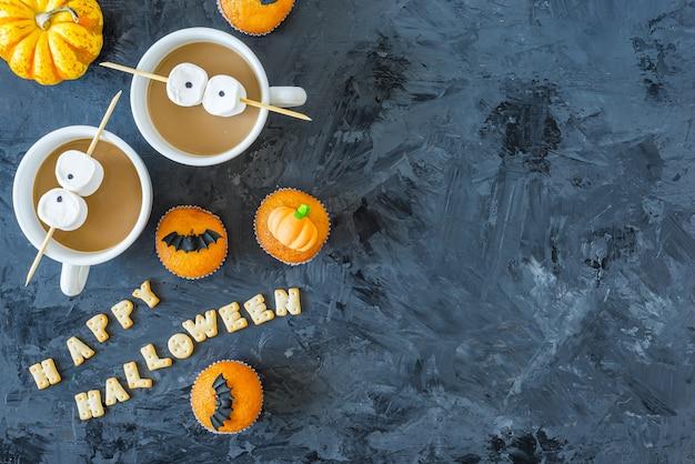 Кексы из тыквы на хэллоуин с чашками кофе и глазами зефира, копией пространства