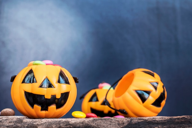Halloween pumpkin face buckets with colorful candy inside on old wooden plank